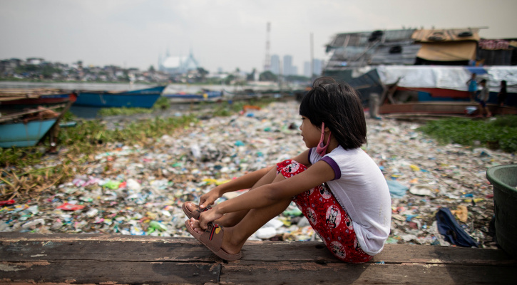 A girl sits on a piece of wood as she looks out to a trash-filled Manila Bay near her home Oct. 6, 2020, during the COVID-19 pandemic. (CNS photo/Eloisa Lopez, Reuters)