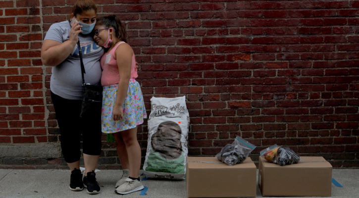 Sandra Cruz of Chelsea, Mass., waits for a ride with her daughter after picking up free groceries from a food pantry July 22, 2020. This year has been a grim and sobering time for many. (CNS photo/Brian Snyder, Reuters)