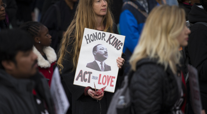 A woman holds a placard with an image of the Rev. Martin Luther King Jr. during a silent prayer walk near his memorial in Washington April 4, 2018. (CNS photo/Tyler Orsburn)