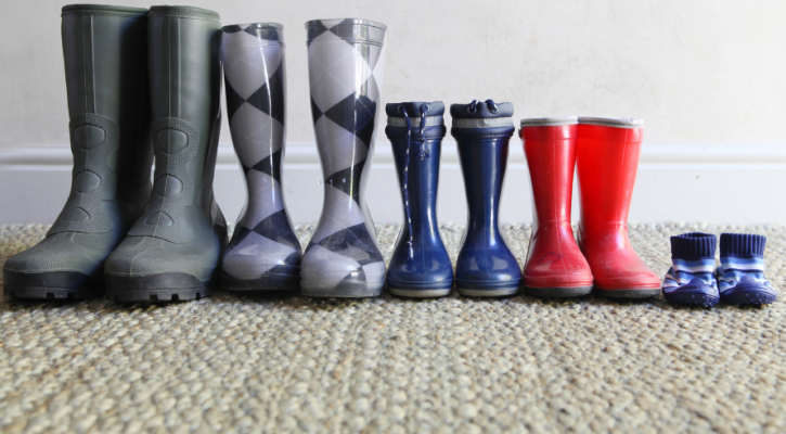 Photo by Brenda Veldtman of five pairs of rain boots lined up together, from adult size to infant. Minute Meditations.