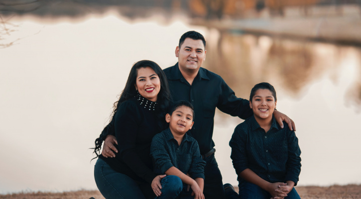 Family posing by water/Photo by Gabriel Tovar on Unsplash